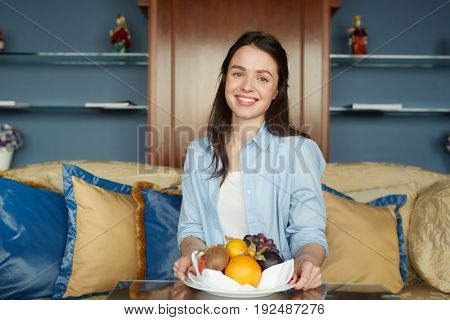 Happy woman with fruits sitting in hotel room