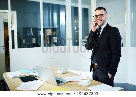 Happy agent in suit calling in office