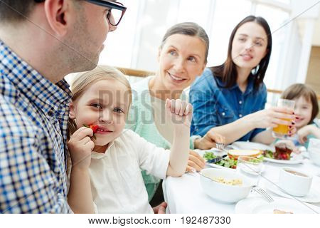 Cute girl eating fresh strawberry for breakfast with her family near by
