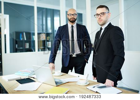 Serious businessman and his co-worker looking at camera