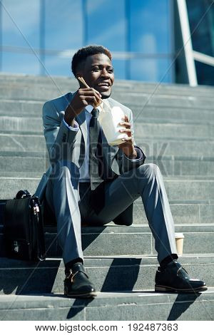 Happy businessman with chopsticks eating food brom box on staircase
