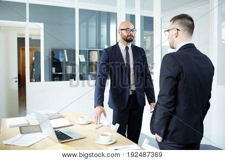 Two elegant employees having talk in office