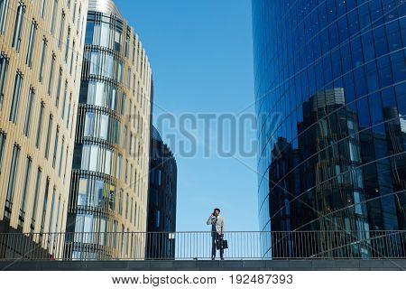 Modern trader calling against blue sky between skyscrapers