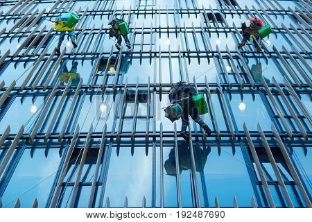 Several workers cleaning modern building