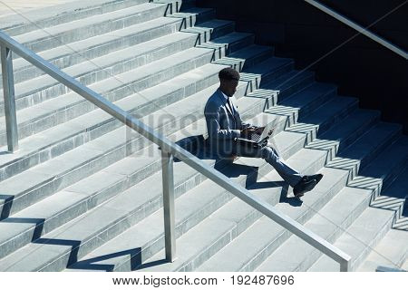 Businessman with laptop sitting on staircase in urban environment and networking