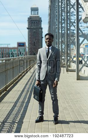 Businessman in suit standing by urban road