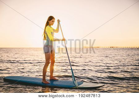 Perfect slim woman stand up paddle surfing in ocean with beautiful sunset colors