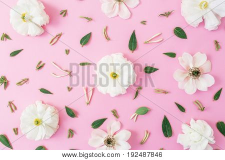 Floral pattern of white flowers and leaves on pink background. Floral background. Flat lay, top view.