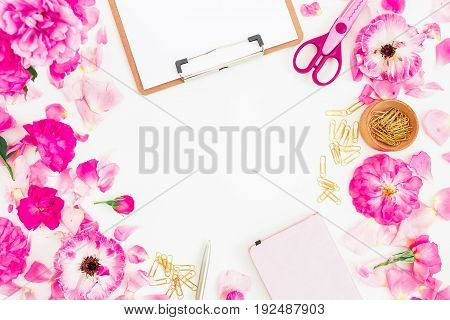 Stylish pink workspace with clipboard, notebook, rose flowers and accessories on white background. Flat lay, top view.