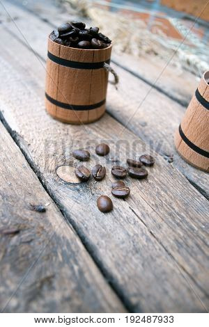 Coffee beans in a barrel on a wooden
