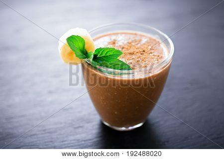 Tasty chocolate banana smoothie on dark background. Fresh milkshake and mint