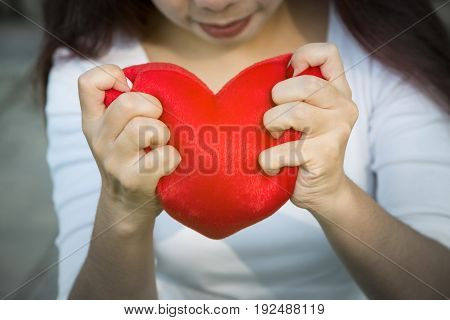 Asian lady hands holding red soft heart small pillow tightly to show her strong feeling of love on Valentines day soft sunlight and selective focus