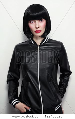 Beautiful slim brunette with bob haircat and stylish makeup in vintage leather jacket