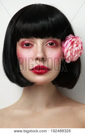 Portrait of young beautiful brunette with bob haircut and stylish vintage red makeup