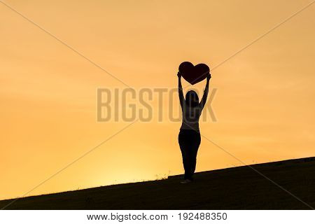 Silhouette of asian lady standing on hill and holding heart with two hands during sunset time to show her love on Valentines day selective focus