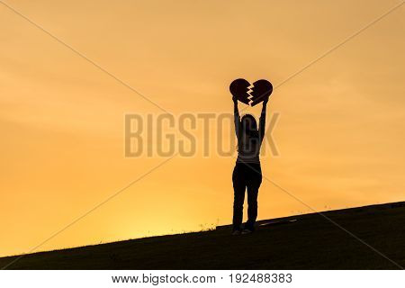 Silhouette of asian woman standing on hill and holding broken heart with two hands during sunset time to show her love on Valentines day selective focus