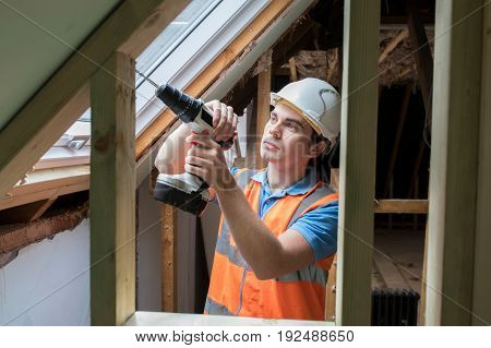 Construction Worker Using Drill To Install Replacement Window