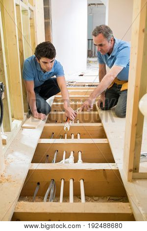 Plumber And Apprentice Fitting Central Heating Together