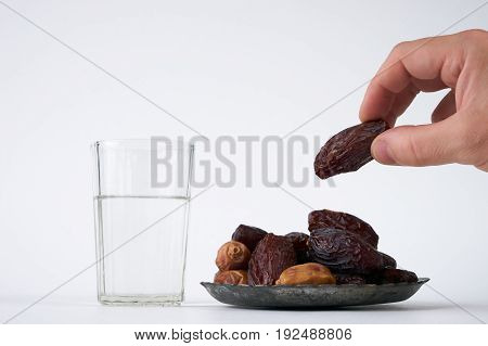 Dates in palm of hand ready to serve for Iftar. Conceptual photo of Ramadan food. Ramadan activities dates glass of water isolated on white background with copy space.