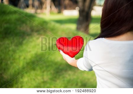Asian woman holding red soft heart pillow with left hand at park as background to show her love on Valentines day concept with warm sun light