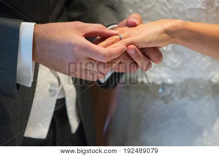 Close Up Of Groom Putting Wedding Ring On Bride's Finger
