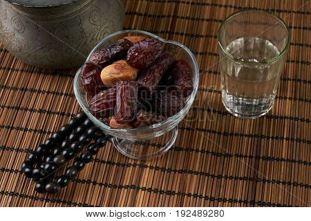 Dates with glass of water for iftar on wooden board for ramadan month. Islamic prayer rosary beads on wooden table. Islamic religion concept.