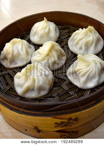 Famous China Shanghai local snack food soup dumplings, xiaolongbao, in a bamboo steamer with thin skin wrapped tasty soup and pork fillings inside.