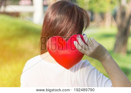 Asian woman holding red soft heart pillow with one hand over shoulder at park as background to show her love on Valentines day concept with warm yellow sun light