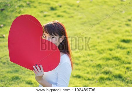 Asian woman holding big red heart shape over her face on green yard background to show her love on Valentines day concept with warm yellow sun light