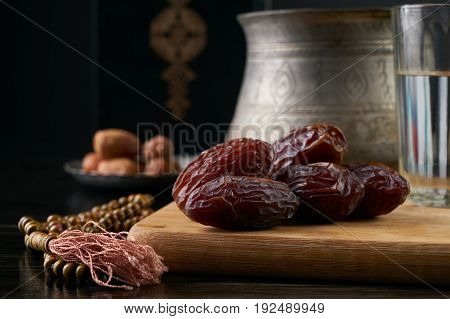 Silver bowl full of dry dates glass of water for iftar and prayer rosary beads with holy Koran on black background. Ramadan month. Islamic religion concept.