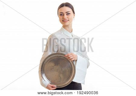 Beautiful girl smiling on camera and holding a silver trey isolated on white background
