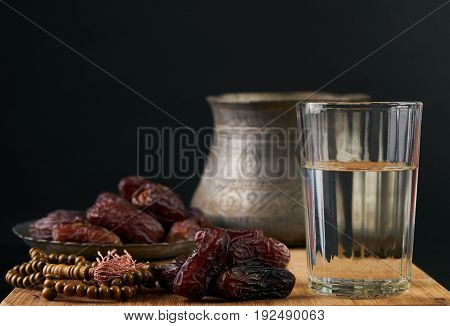 Silver bowl full of dry dates glass of water for iftar and prayer rosary beads on wooden board isolated on black background. Ramadan month. Islamic religion concept.