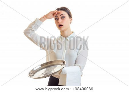 Surprised woman waitress with trey in hands looking at the camera isolated on white background