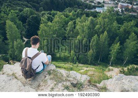 young man sits on the peak and texting,