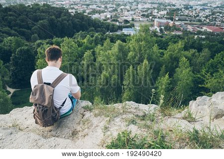young man sits on the peak and thinking