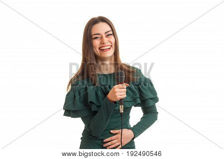 Happy woman laughing with microphone in hands in green dress isolated on white background