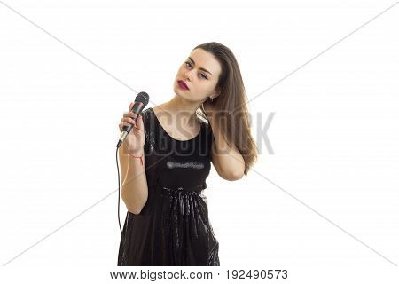 Woman in bright black dress with microphone in hands isolated on white background