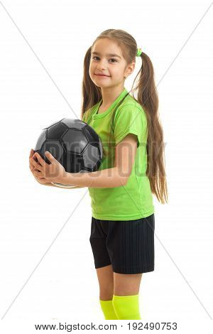 vertical portrait of cutie little girl in green shirt holding a soccer ball in hands isolated on white background