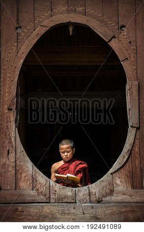 NYAUNGSHWE, MYANMAR - OCT 05 2014: Myanmar novice reading the book in the Shwe-Yaunghwe monastery the big window temple in Myanmar.