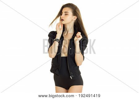 Sensual young woman in black jacket and high panties with closed eyes isolated on white background