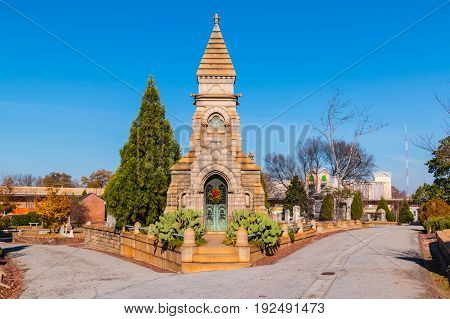 Atlanta, Georgia, USA - December 22, 2016: Luxury crypt on the crossroad and tombstones on the Oakland Cemetery in sunny autumn day