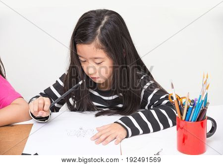 Asian girl kid concentrates on drawing cartoons by pencil in art class over table and light wall background with friends