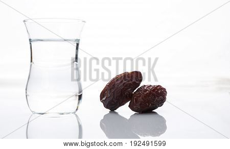 Close-up of traditional glass of water with dry dates for iftar party holidays isolated on white background with copy space. Ramadan ramazan kareem. Islamic religion concept.