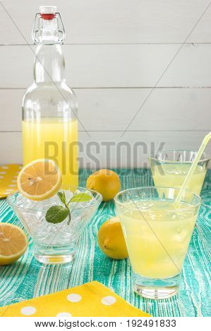 lemonade or limonchello in yoke stopper bottle beverage in glasses sherbet glass with ice cubes lemon fruits on turquoise colored wooden table