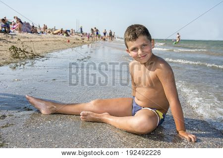 In summer a suntanned boy sits on the beach by the sea.
