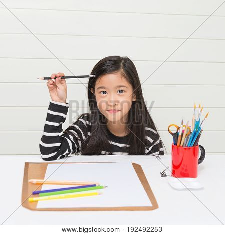 Happy Asian girl kid thinking about what to draw and holding pencil in hand on white table with color pencils paper and cork board over light wall background