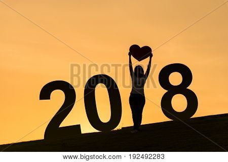 2018 new year silhouette of asian lady standing on hill and holding heart over her head with two hands during sunset time to show her love
