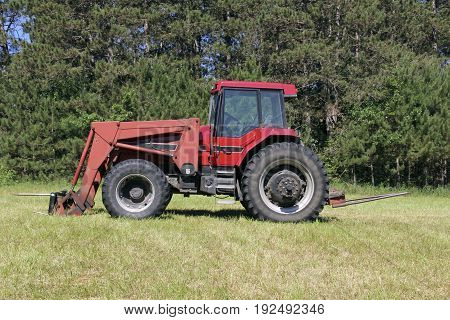 Red farm tractor on a green grass pasture with a woods in the background