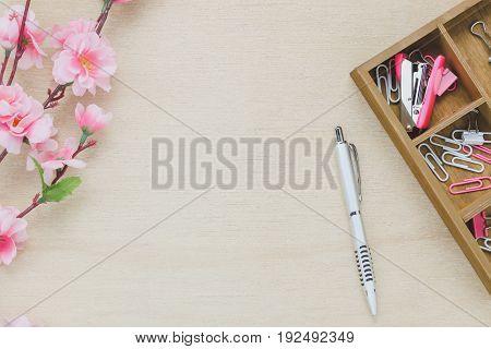 Top view business office desk background.The silver pen coffee beautiful pink flower wood shelf staple clip on wooden table background with copy space.