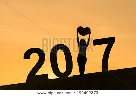 2017 new year silhouette of asian lady standing on hill and holding heart over her head with two hands during sunset time to show her love